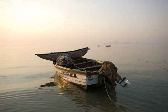 Monkey Bay, Southern Malawi, a dug out canoe on front of a speed boat